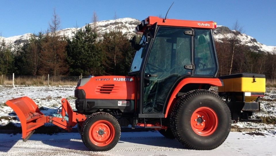 snow clearing and gritting tractor used to clear snow and add grit to surfaces